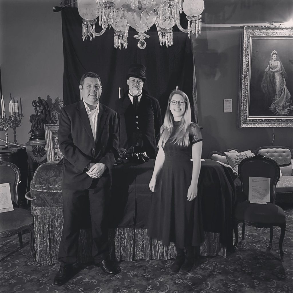 Three people standing in front of a coffin in a gilded-era mansion